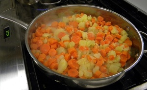 Potatoes and carrots are fried and set aside