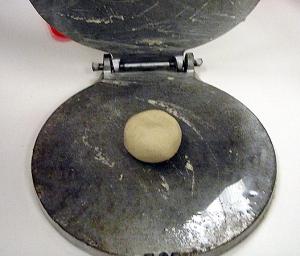 ball of masa dough in a tortilla press