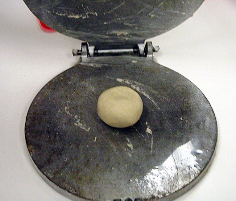 ball of masa dough in a tortilla press
