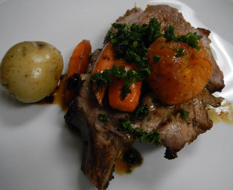 Roasted pork rack with mandarins, potatoes and carrots