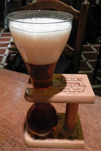 an official Kwak glass, positioned in a unique wood container