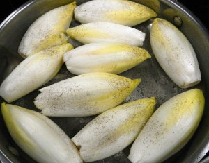 Belgian endives salt and peppered and in the pan