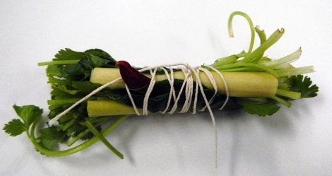the bouquet garni made up of cilantro stems, lime leaves, 1 red Thai chile and the tough leftover tops of lemongrass