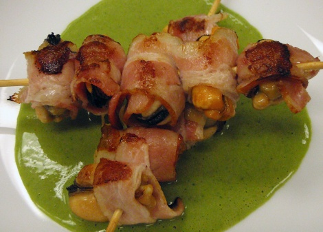 an appetizer of bacon & mussel on skewers with basil cream