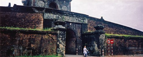 a bicyclist rides through an archway in the imperial wall in Hue, Vietnam
