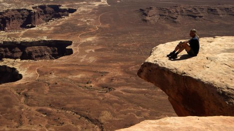 sitting on the edge of the Island in the Sky in Canyonlands National Park