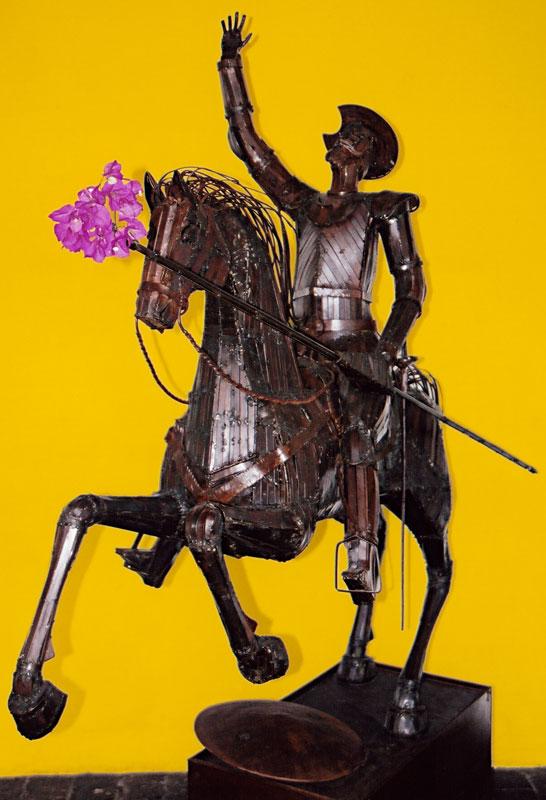 pink buganbilla on a statue of Don Quixote