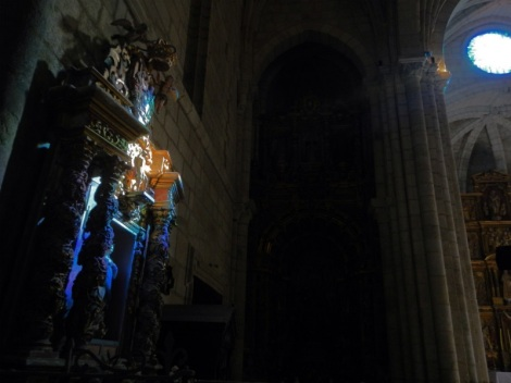Altar highlighted by the coloured light of the stained glass windows.