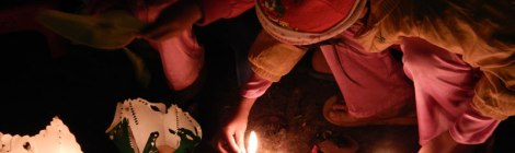 In Hoi An, two little girls in Santa hats lighting floating lanterns