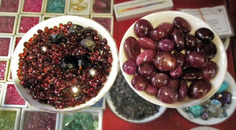 Rubies and star rubies for sale. On the shelf beneath them are more gemstones, mostly more rubies as well as greyish sapphires and other stones.