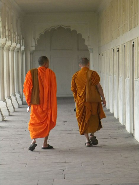 Buddhist monks in saffron robes strolling down a hallway at Agra Fort