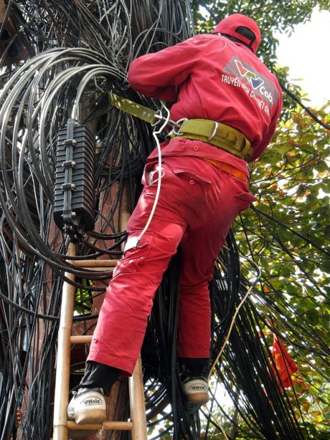 In Hanoi, a linesman works on a zillion electrical wires all at one time!