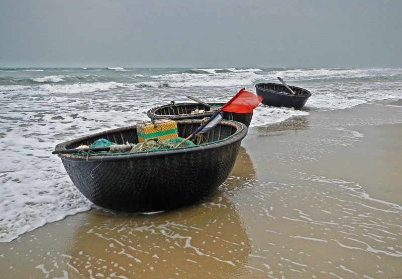 Fishing coracles surf in on the waves at the beach on Hoi An