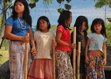 Guarani indigenous girls pounding out a rythmn with sticks up at Iguazu Falls in Argentina
