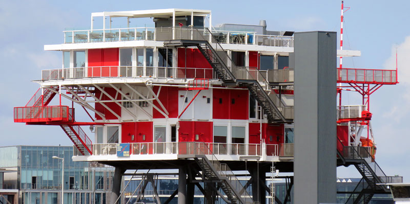 Red & white geometric architecture on stilts atop a wharf overlooking the river