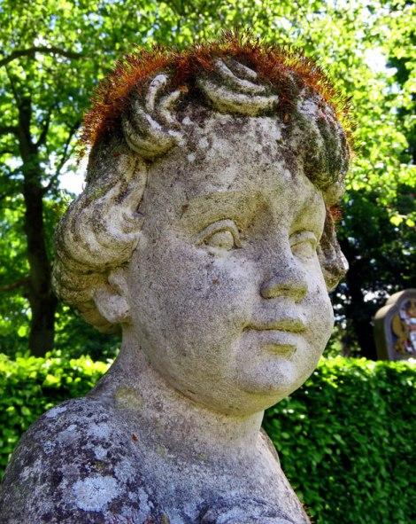 Face of a cherub with a mossy hairdo at Kasteel de Haar near Utrecht, Holland.