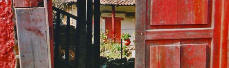 Patzcuaro red doors leading into an inner courtyard and garden