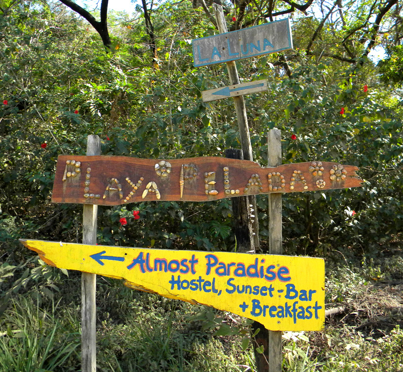 Sign indicates this way to 'Playa Pelada', that way to 'Almost Paradise' (Costa Rica)