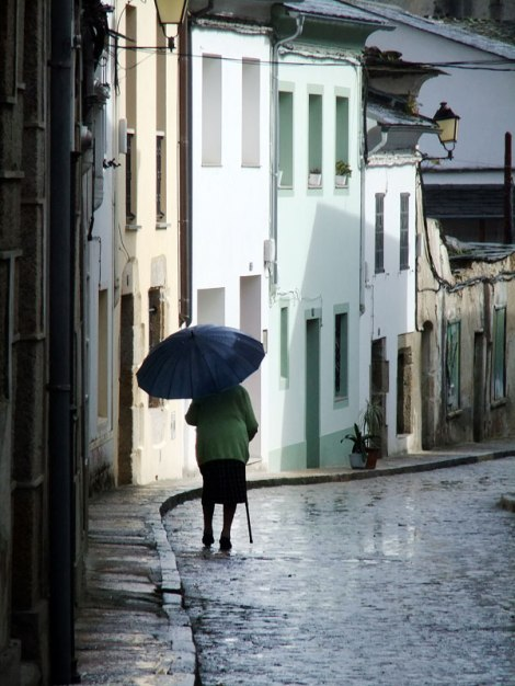 An old lady walking in the rain in Mondoñedo