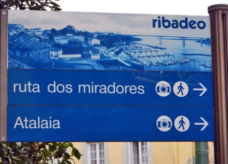 Walks along the busy waterfront of Ribadeo on the northwest coast of Galicia in Spain