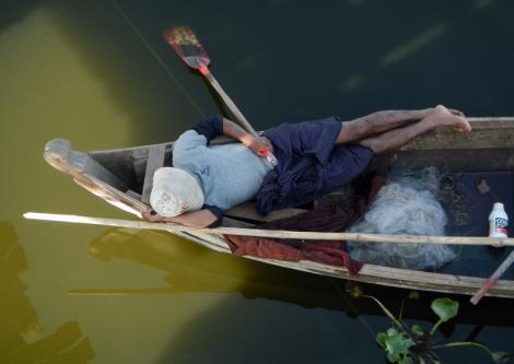 Napping in a boat under U Bein Bridge in Mandalay, Myanmar.