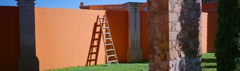 Ladder up against the orange wall built into the aqueduct in Zacatecas, Mexico
