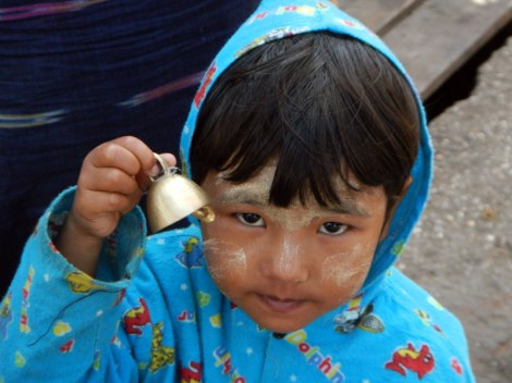 Little girl with a golden bell in Yangon, Myanmar