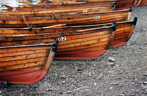 A lineup of wooden boats on a beach in England's Lake District