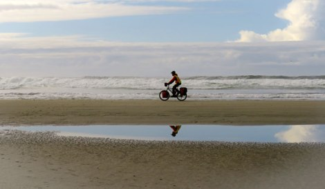 A bicyclist rides along Long Beach in the Pacific Rim National Park on Vancouver Island, BC, Canada