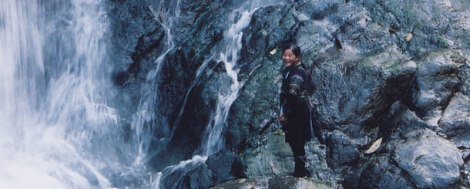 A hilltribe girl plays in the waterfall in the mountainous region near Sapa in Vietnam