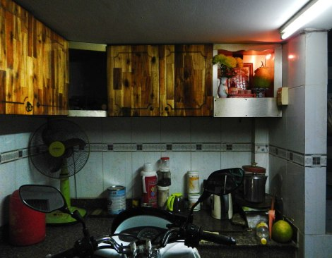 Kitchen in HCMC's District 1 with the requisite altar and motorbike parking