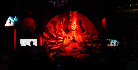 Red lights shine on a many armed goddess in a Puerto Vallarta Club, Mexico