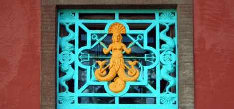 Colourful window grating with a two-tailed mermaid in Portmeirion, Wales