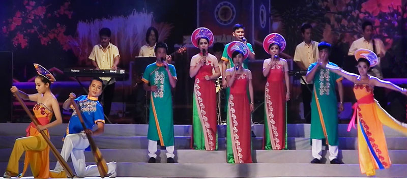 Singers in traditional Vietnamese costumes on the stage in the HCMC night, Vietnam