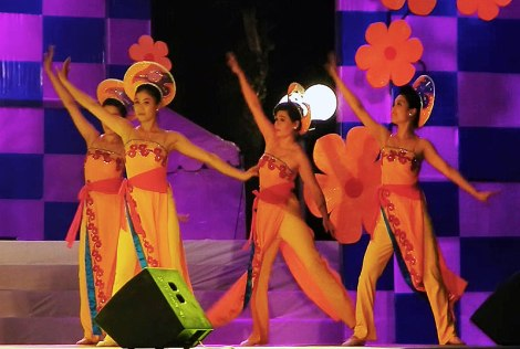 Dancers in traditional yellow costumes on the stage in the HCMC night, Vietnam
