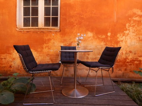 Table and chairs against an orange wall in Copenhagen, Denmark