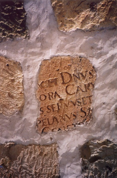 Reusing old stone carved with writing for a wall in Oaxaca, Mexico