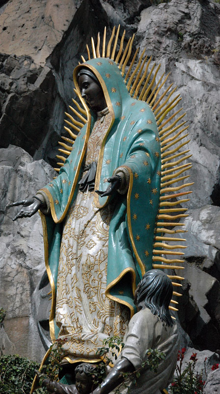 Statue of the dark virgin of Guadalupe, Mexico's patron saint, wearing a blue cloak studded with stars and surrounded by sun rays