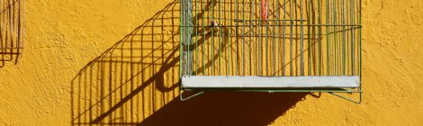 A cage and its shadow on a yellow wall in Puebla, a UNESCO Heritage site in Mexico.