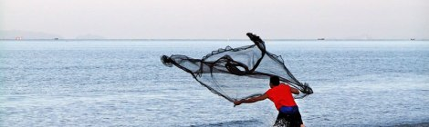 Fisherman casting his net into the Andaman Sea at Koh Lanta, Thailand