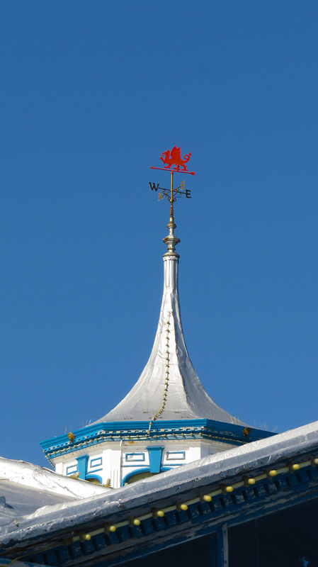 A weathervane with the Welsh red dragon atop one of silver-roofed buildings on Llandudno Pier in Wales
