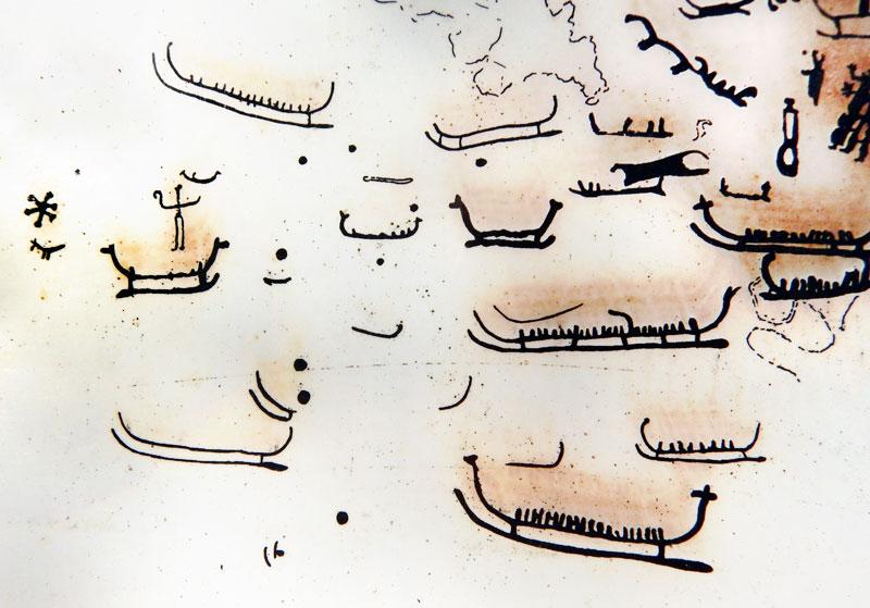 Boats on a sign explaining the glyphs on a 6 Km Petroglyph Walk Amongst Farmer's Fields in Tanum, Sweden