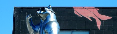 a silver bear with sunglasses waves from a roof deck backdropped by a Haida-inspired mural.